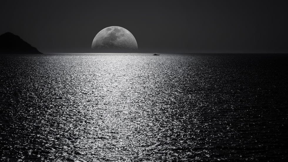moon over the ocean with boat in the distance